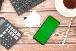 teléfono inteligente y tarjeta de crédito en la mesa de madera foto
