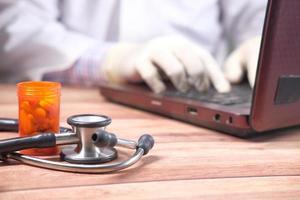 Pastillas y estetoscopio, doctor escribiendo en segundo plano.