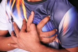 hombre sujetando el pecho con dolor foto