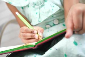 niño escribiendo en un cuaderno foto