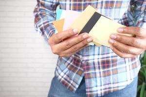 hombre sosteniendo sobres de colores