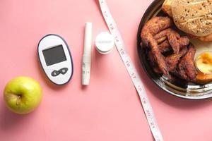 Herramientas de medición para diabéticos con manzana y harina sobre fondo rosa