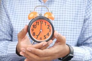 Man's hand holding orange alarm clock photo