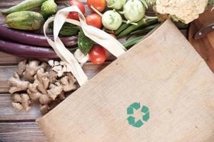 Bolsa de compras reutilizable con verduras en la mesa. foto