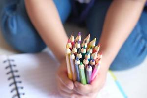 Close up of a child's hand holding many colorful pencils