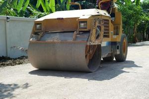 Heavy steel wheel of the road roller moving on the crash stone road under construction photo