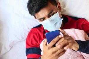 Hombre enfermo en mascarilla quirúrgica con teléfonos inteligentes.