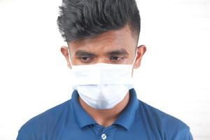 Un joven con máscara protectora sobre fondo blanco. foto