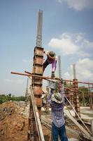 Ratchaburi, Thailand 2018 - Group of workers build the foundation of a house by pouring the mixed cement into the wooden model at the construction site photo