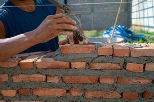 Hands of worker holds the trowel and installs bricklayers photo