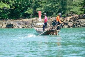 Krabi, Thailand 2019 - Fishermen drive the traditional long-tail boat and find fish by tools photo