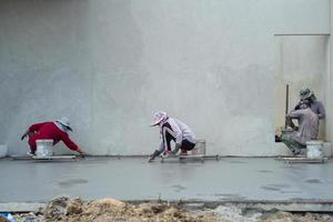 Back portrait of a group of workers using trowels for flooring the cement surface