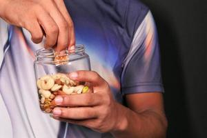 Man's hand eating mixed nuts from jar photo