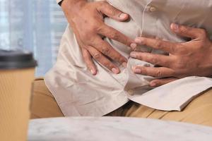 Man suffering stomach pain sitting on sofa photo