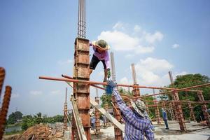 Ratchaburi, Tailandia 2018: un grupo de trabajadores construye los cimientos de la casa vertiendo el cemento mezclado en el modelo de madera en el sitio de construcción foto