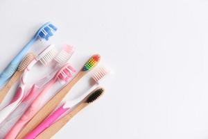 Cepillos de dientes de colores sobre fondo blanco con espacio de copia foto