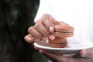 Chocolate macaroons on a white plate photo