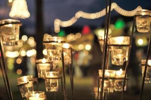 Selective focus on candles in small glasses with blurred bokeh lights in background