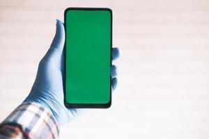 Mano en guantes de látex verde sosteniendo un teléfono inteligente con pantalla verde foto