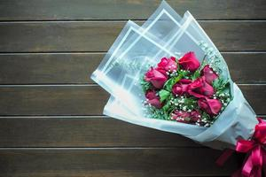 Top view bouquet of bloomed red roses on the wooden table