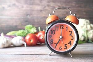 Alarm clock and fresh vegetables on table with copy space photo