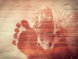 Abstract footprint on the dusty wooden floor photo