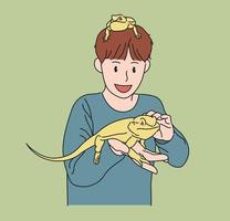 A boy is playing with his pet lizard on his hand. hand drawn style vector design illustrations.