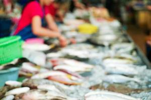 Blurred picture of raw fresh fish on the tray for selling in the market with blurred seller