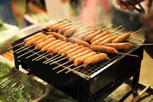 Closeup row of bbq sausages on the charcoal grill with smoke