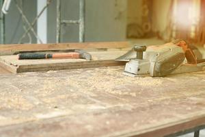 El enfoque selectivo en herramientas de carpintería en el escritorio de madera sucia con aserrín foto