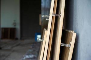 El enfoque selectivo en las bisagras de acero inoxidable en la puerta de madera esperando la instalación foto