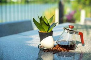 Portrait of glass jar with coffee inside and empty cup on table at the outdoor garden