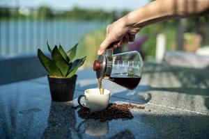 Hand of barista pouring the coffee from the glass jar into the cup at the outdoor garden