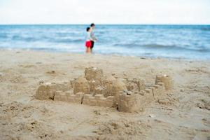 The sandcastle built by using the mold with blurred people in the background photo