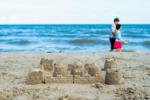 The sandcastle built by the mold with blurred people walking on the beach in background photo