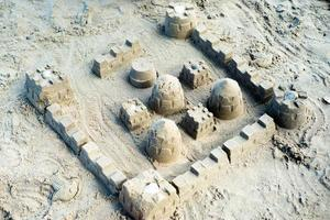 The sandcastle built by using the mold on the beach photo