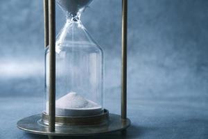 arena que fluye a través del reloj de arena en la mesa foto