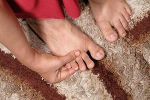 mujer masajeando pies foto
