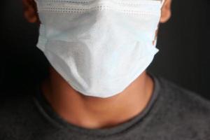 Cerca del hombre con mascarilla protectora aislado en negro foto
