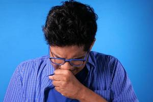 Hombre enfermo en vestido casual tos, fondo azul foto