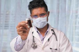 doctor en máscara sosteniendo una botella de pastillas foto
