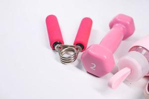 Mancuerna de color rosa y botella de agua sobre fondo blanco. foto