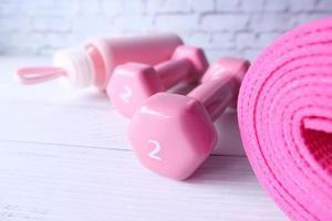 Mancuernas de color rosa y colchonetas para ejercicios sobre fondo blanco. foto
