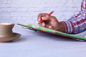 Cerca de la mano del hombre escribiendo en el bloc de notas