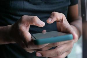 Close up of young man's hand using smart phone photo