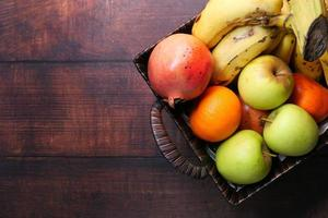 Top view of apples, bananas, and oranges in a bowl on table photo