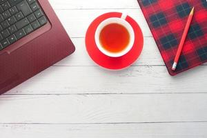 té caliente, computadora portátil y un cuaderno en un escritorio foto