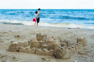 Sandcastle built by using the mold with people walking on the beach in background photo