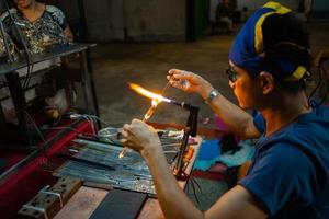 Hua Hin, Thailand 2018 - Worker is making craftsmanship product by melting and blowing the glass bars photo