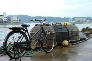 Closeup of a vintage bicycle near traditional fishing tools at the sea port photo